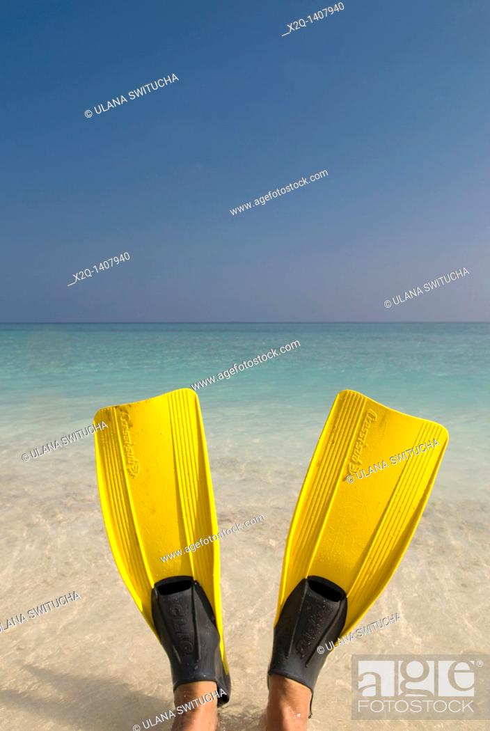 Stock Photo: A person sitting in the ocean wearing Yellow flippers Maldives.