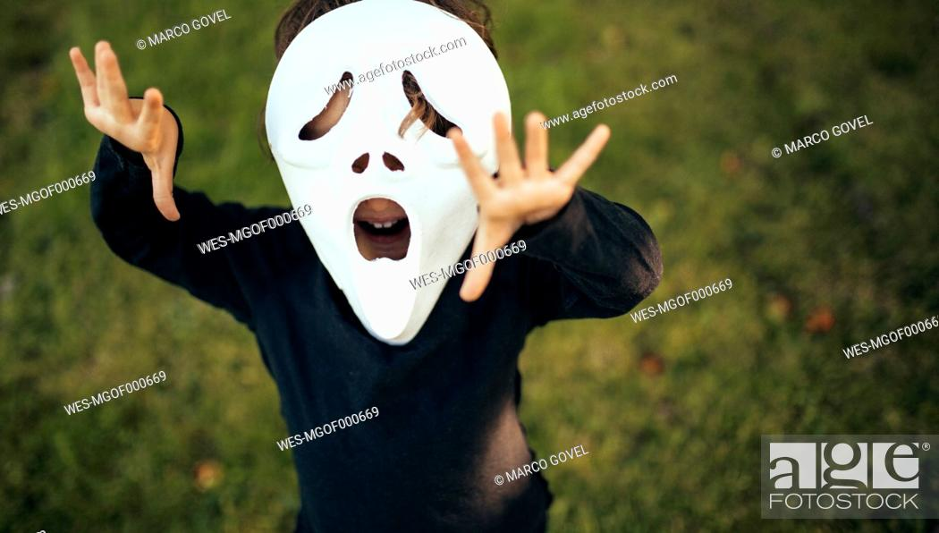 Stock Photo: Girl masquerade with a mask standing on a meadow.