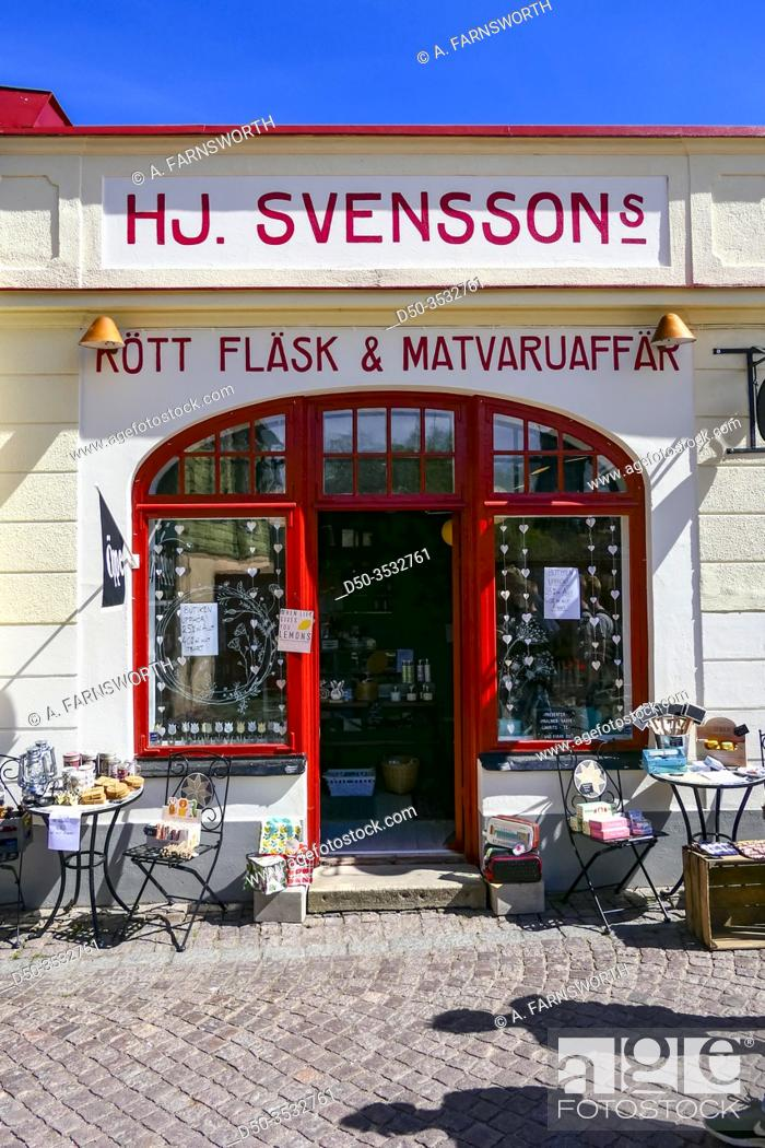 Stock Photo: Soderkoping, Sweden Pedestrians walking on Storgatan in front of a food store, sign says: meat, pork, and food store.