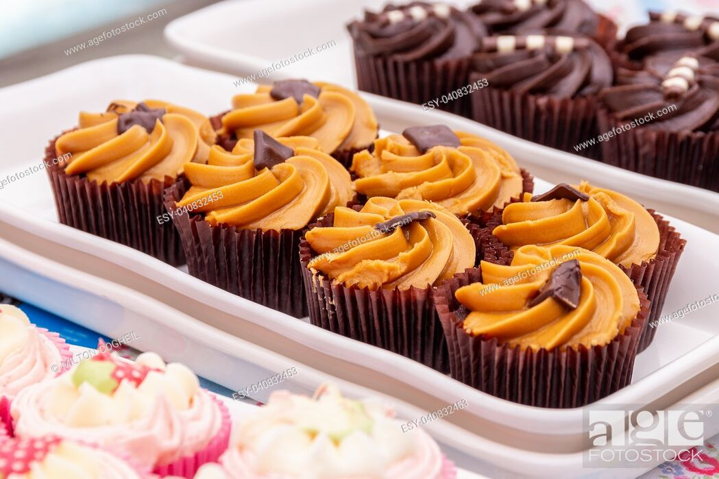 Stock Photo: Homemade orange and chocolate cupcakes on a market stall.
