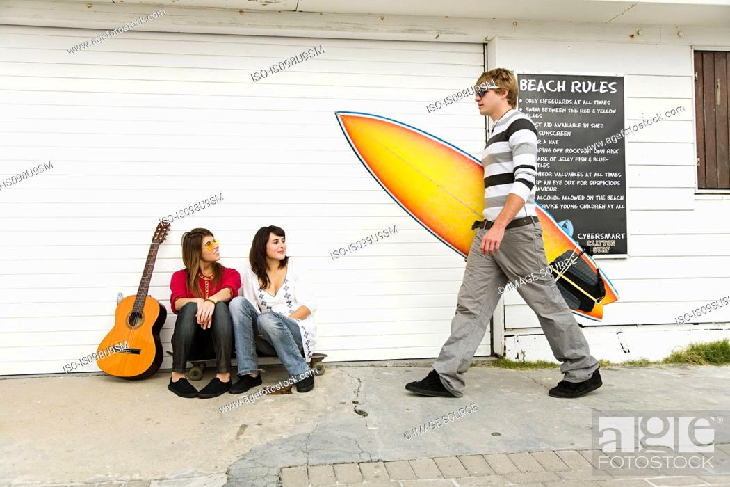 Stock Photo: Two girls watching young man carrying surfboard.