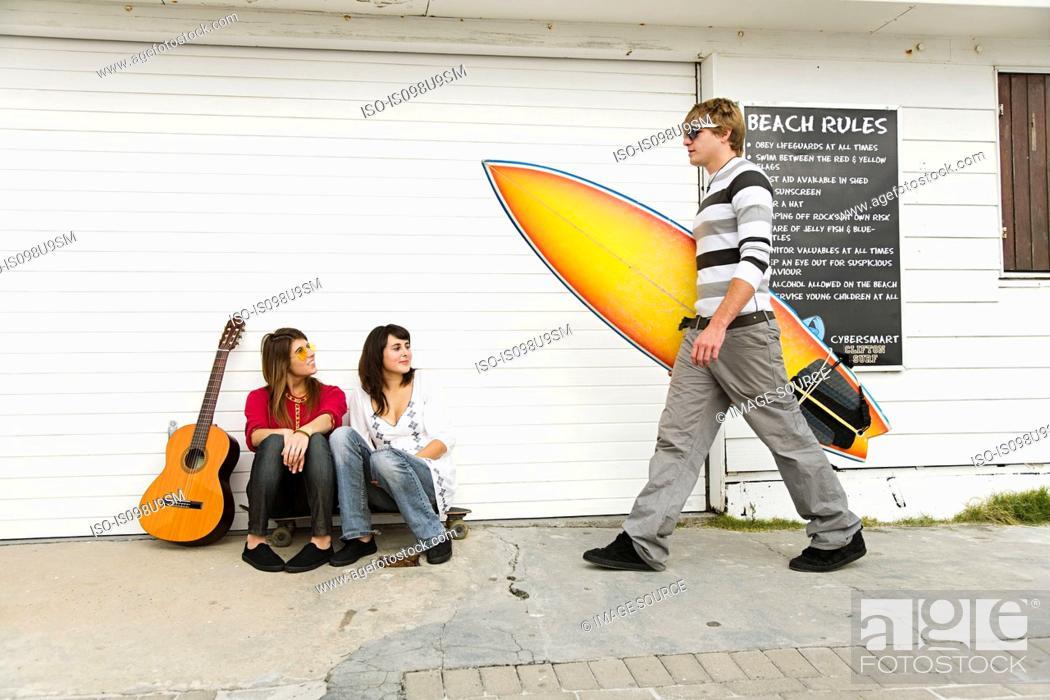 Stock Photo: Two girls watching young man carrying surfboard.