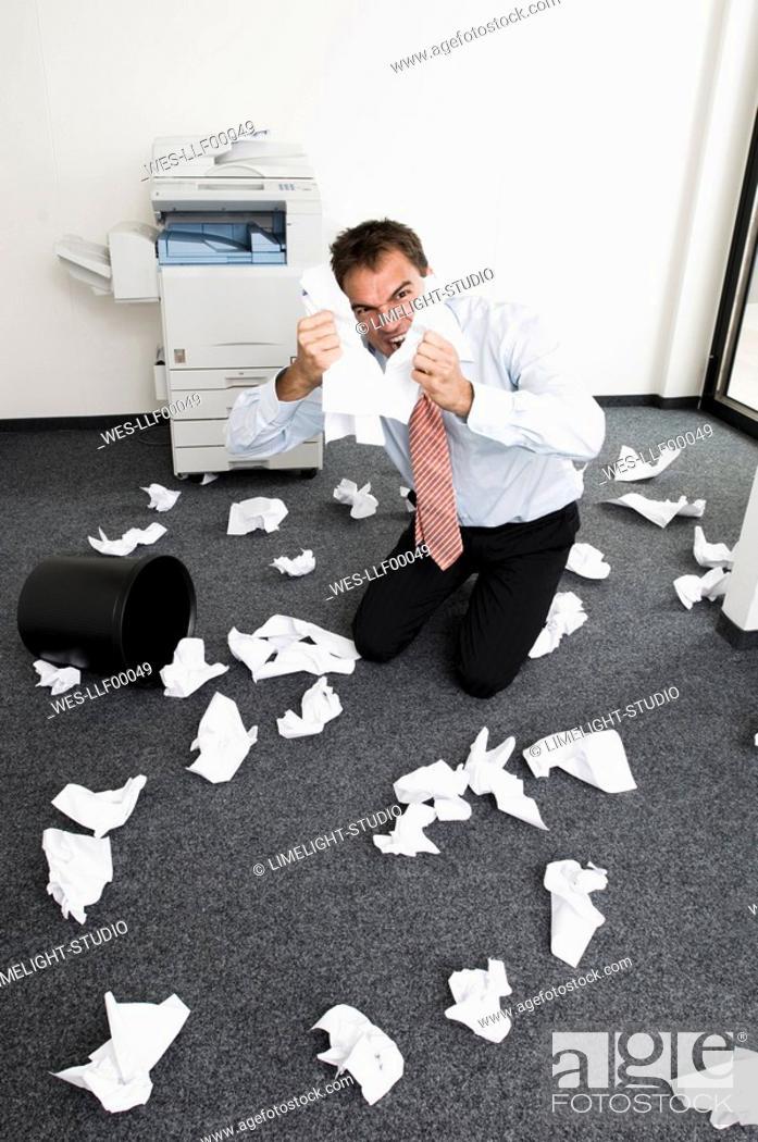 Stock Photo: Businessman kneeling in despair, tearing sheets of paper.