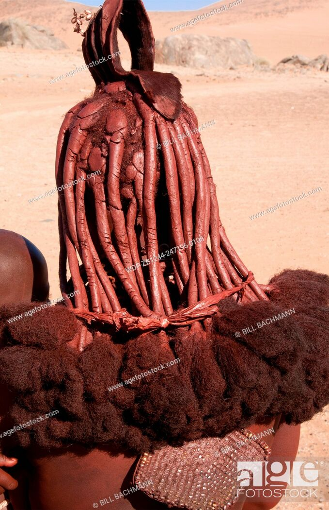 Imagen: Namibia Africa remote nomadic Himba tribe young woman with braids and traditional dress close up of hair in desert of Hartmann Berge in Namib Desert.