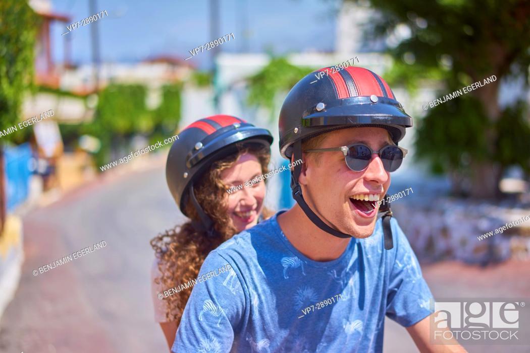 Stock Photo: exhilarated young couple enjoying road trip with moped. Hersonissos, Crete, Greece.