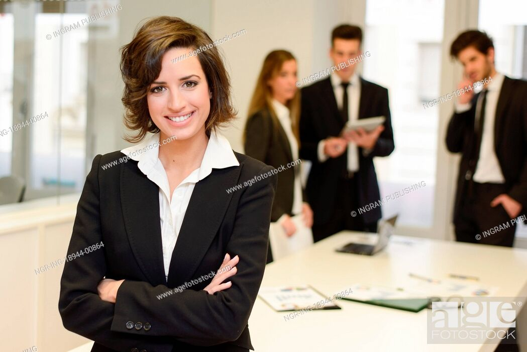Stock Photo: Businesswoman leader looking at camera in working environment. Young woman wearing black blazer jacket.