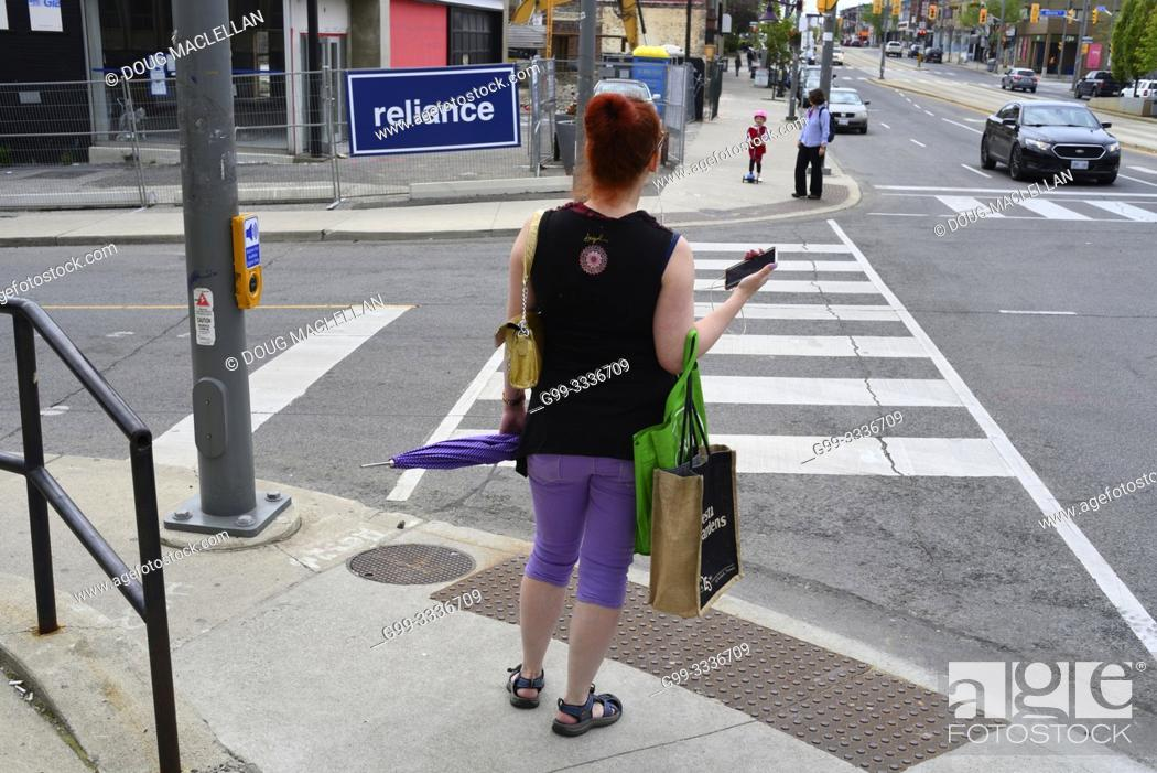 "Stock Photo: A woman in purple pants with a green handbag waits to cross an intersection and a sign spelling ""reliance"", Toronto, Ontario, Canada."