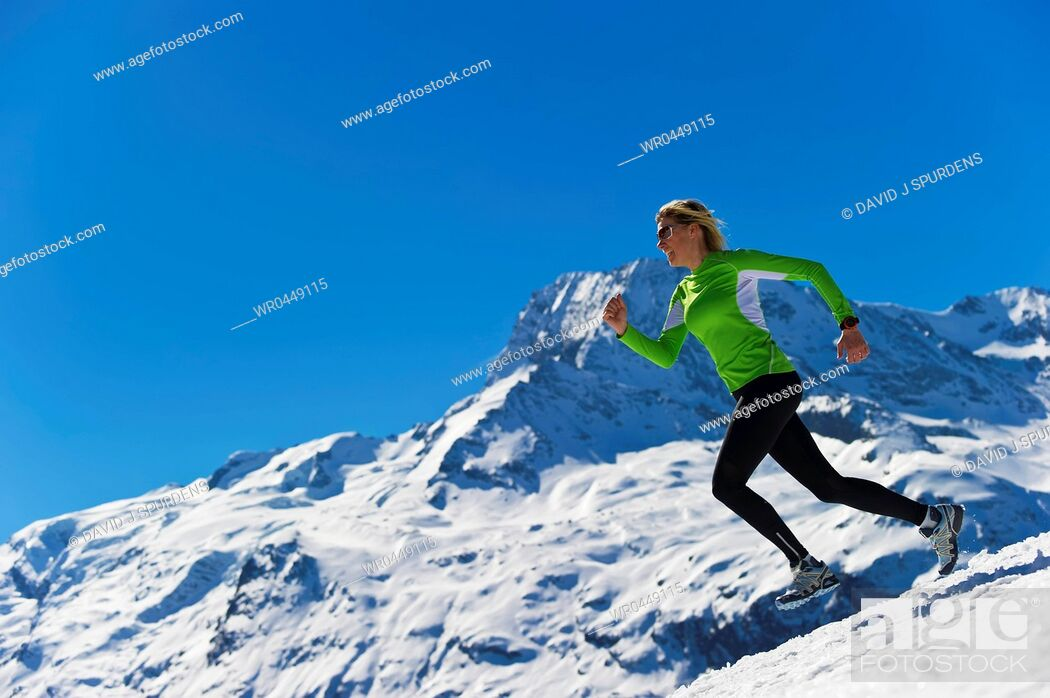 Stock Photo: A woman jogging in high snowy alpine mountains.