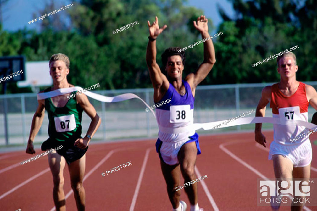 Stock Photo: Portrait of male runners crossing the finishing line in a race.