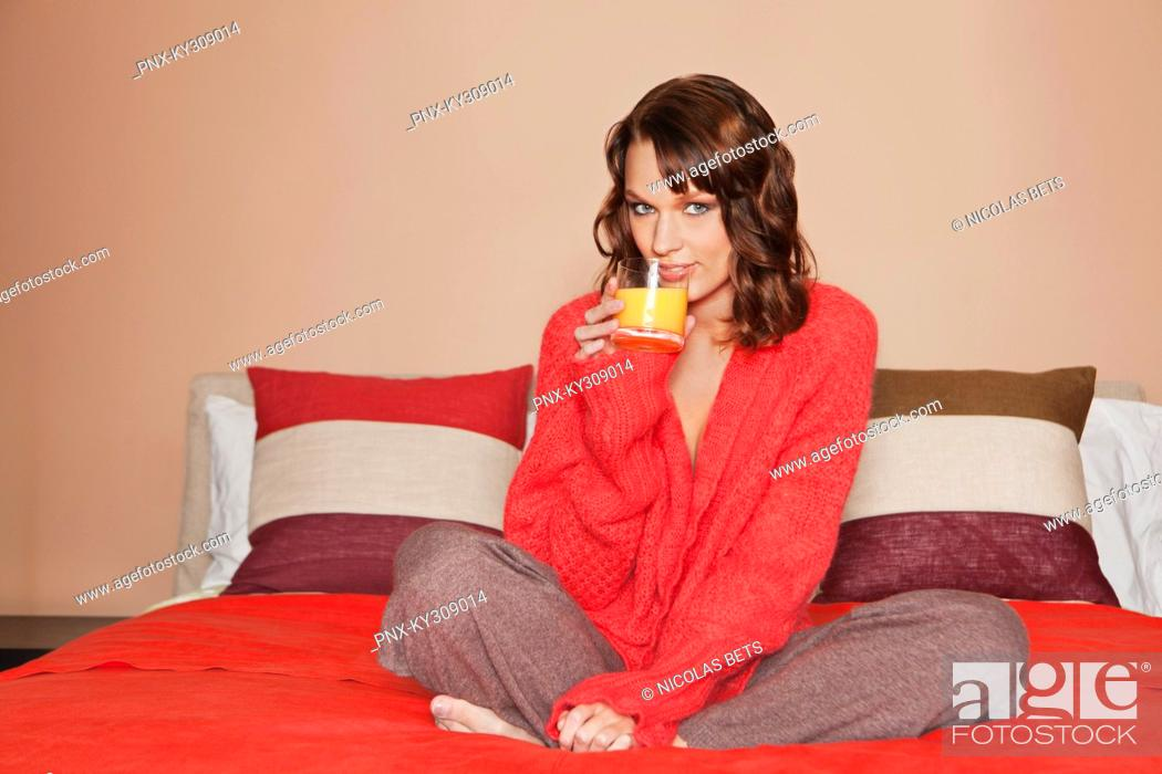 Stock Photo: Young woman drinking orange juice, sitting cross-legged in bed.