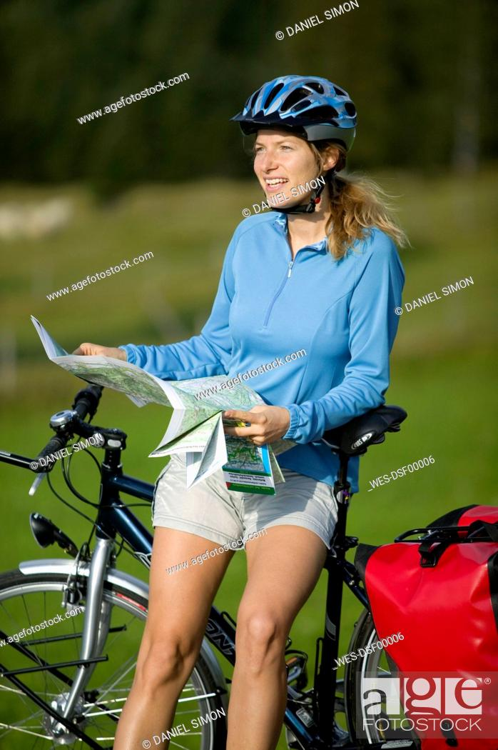 Stock Photo: Germany, Bavaria, Mittenwald, Woman leaning against mountain bike, holding map.