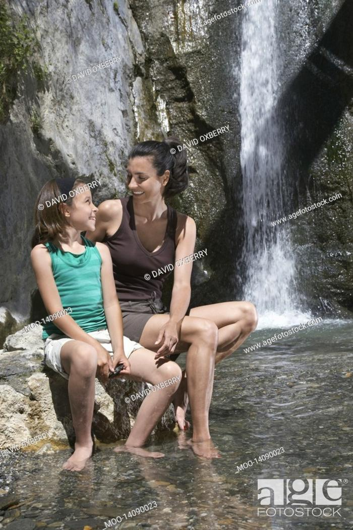 Stock Photo: Mother and daughter 10-12 sitting on rock by river.
