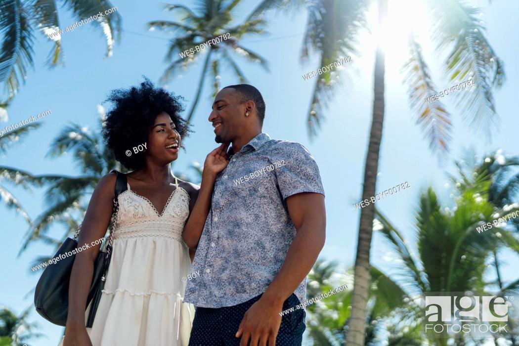 Photo de stock: USA, Florida, Miami Beach, happy young couple at palm trees in summer.