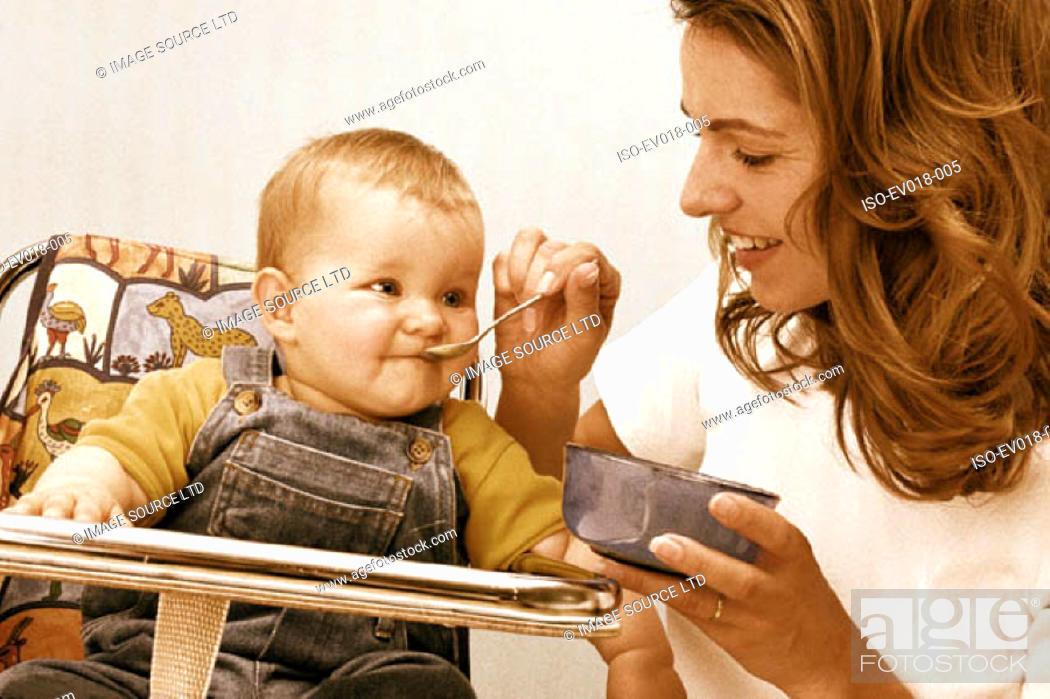 Stock Photo: Mother feeding baby.