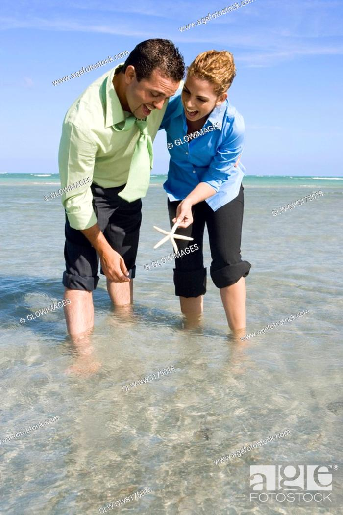 Stock Photo: Mid adult couple playing with a starfish in water.