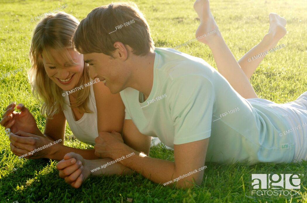 Imagen: Young couple lying in meadow.