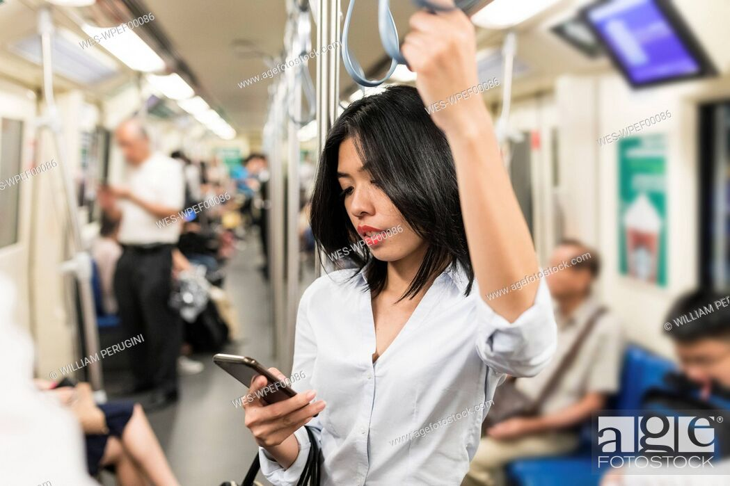 Stock Photo: Businesswoman using cell phone in the subway.
