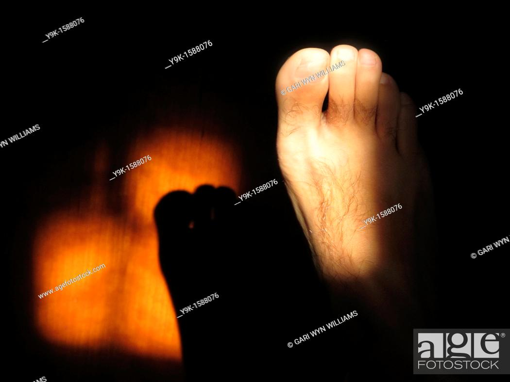 Stock Photo: Shadow of foot on wooden door.