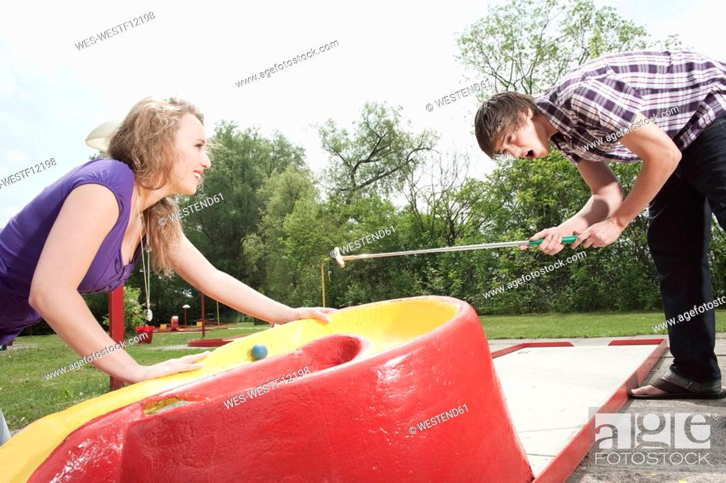 Stock Photo: Germany, Bavaria, Ammersee, Young couple playing mini golf.