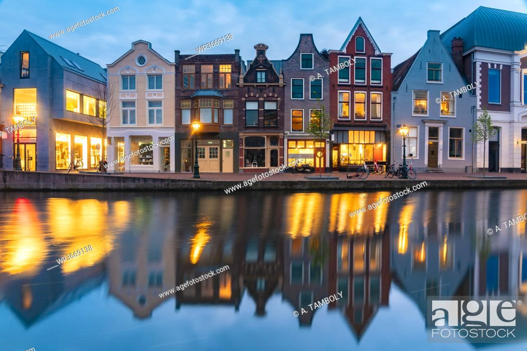 Stock Photo: Netherlands, South Holland, Leiden, Row of historical townhouses reflecting in Rhine canalat dusk.