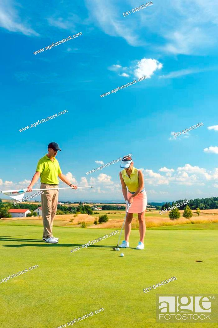 Imagen: Full length of a woman calculating the trajectory of the ball to the hole, while playing professional golf with her male match partner or instructor outdoors in.