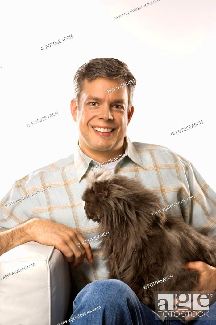 Stock Photo: Mid-adult Caucasian man sitting holding Persian cat.