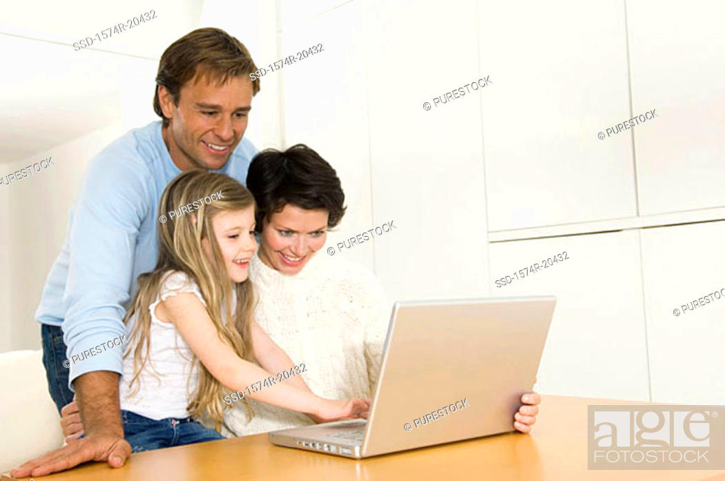 Stock Photo: Girl using a laptop with her parents.