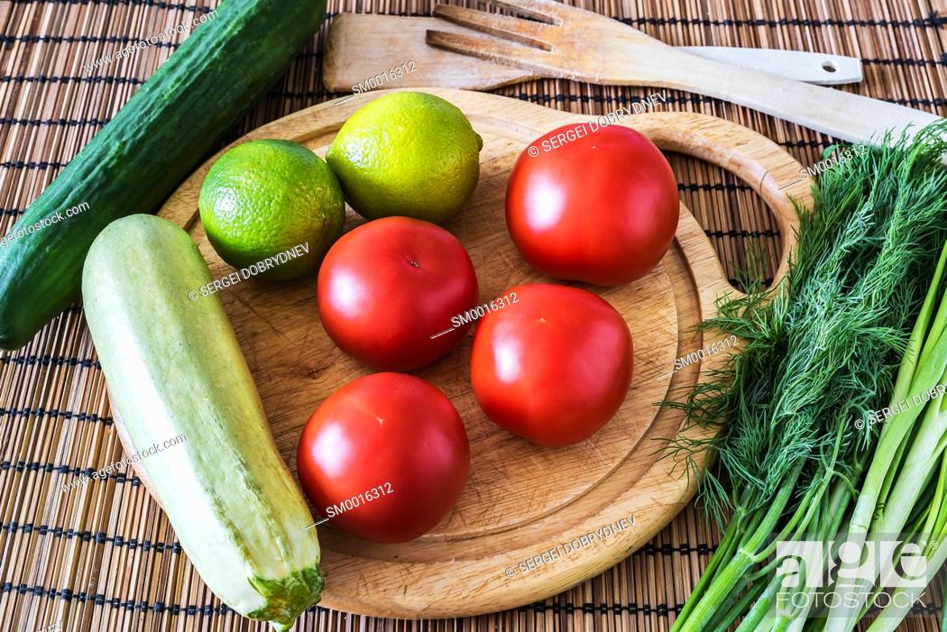 Stock Photo: Tomatoes, cucumber, zucchini, greens, lime and a cutting board lie on the kitchen table.