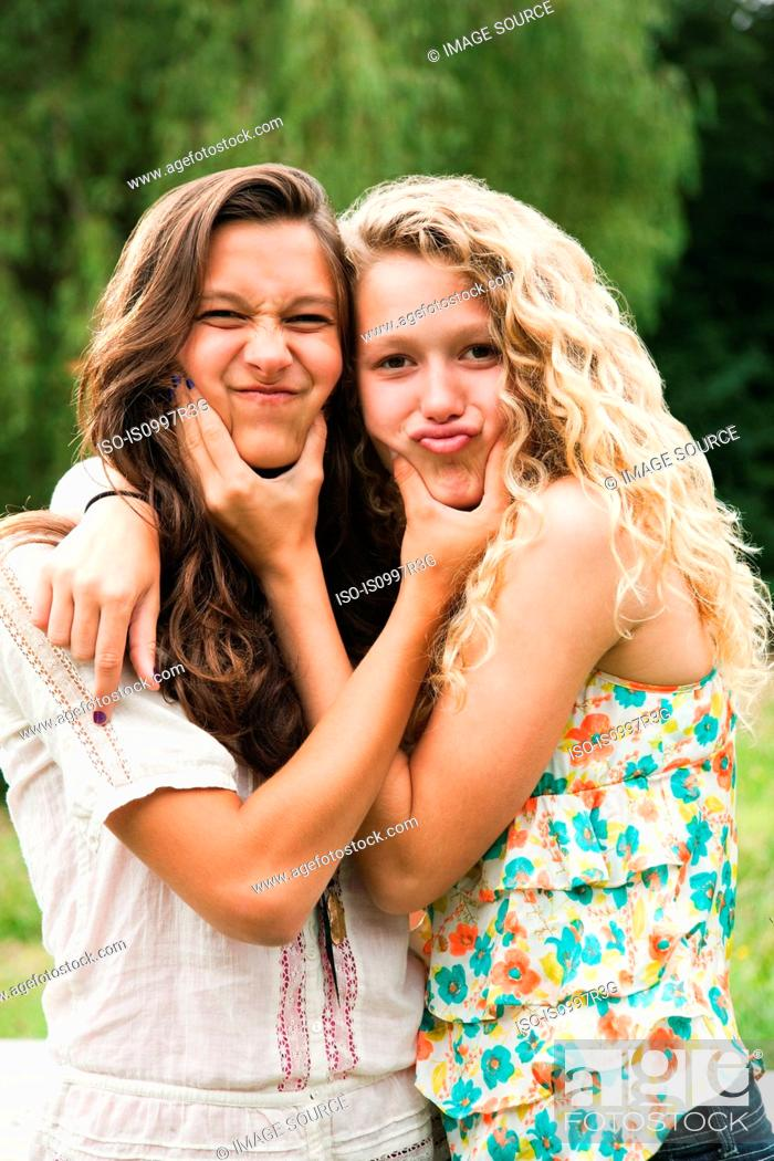 Stock Photo: Two teenage girls fooling around and making faces.
