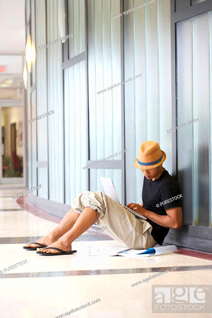 Stock Photo: Side profile of a college student sitting in a corridor and using a laptop.
