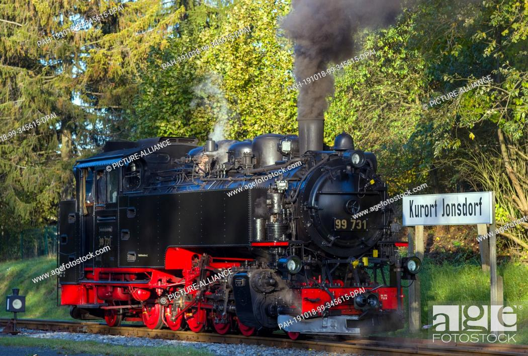 Stock Photo: 10 October 2019, Saxony, Jonsdorf: A steam engine of the Zittau narrow-gauge railway runs into the station of the Kuortes.