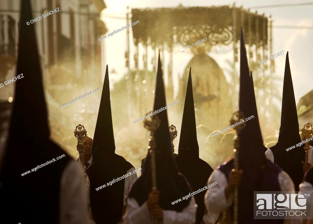 Stock Photo: Penitents walk in front of a throne displaying a sculpture of Our Lady of Sorrows during an Easter Holy Week procession in Carmona village, Seville province.