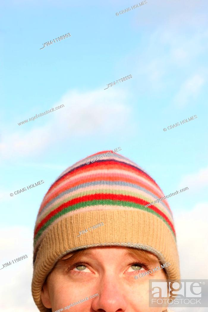 Stock Photo: A young woman in a cosy hat looking upwards toward a blue sky.