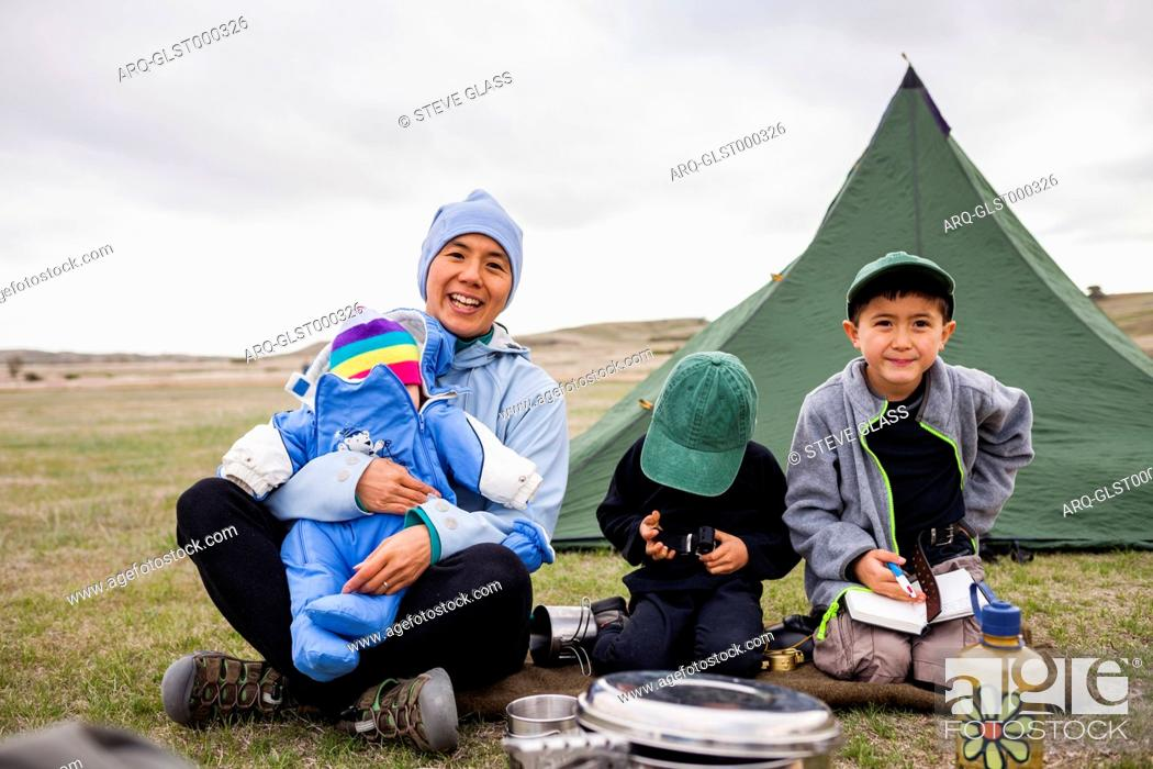 Imagen: A family consisting of a Japanese American woman holding her 6 month baby girl, and 4 year old and 6 year old Japanese American boys sit in front of their tent.