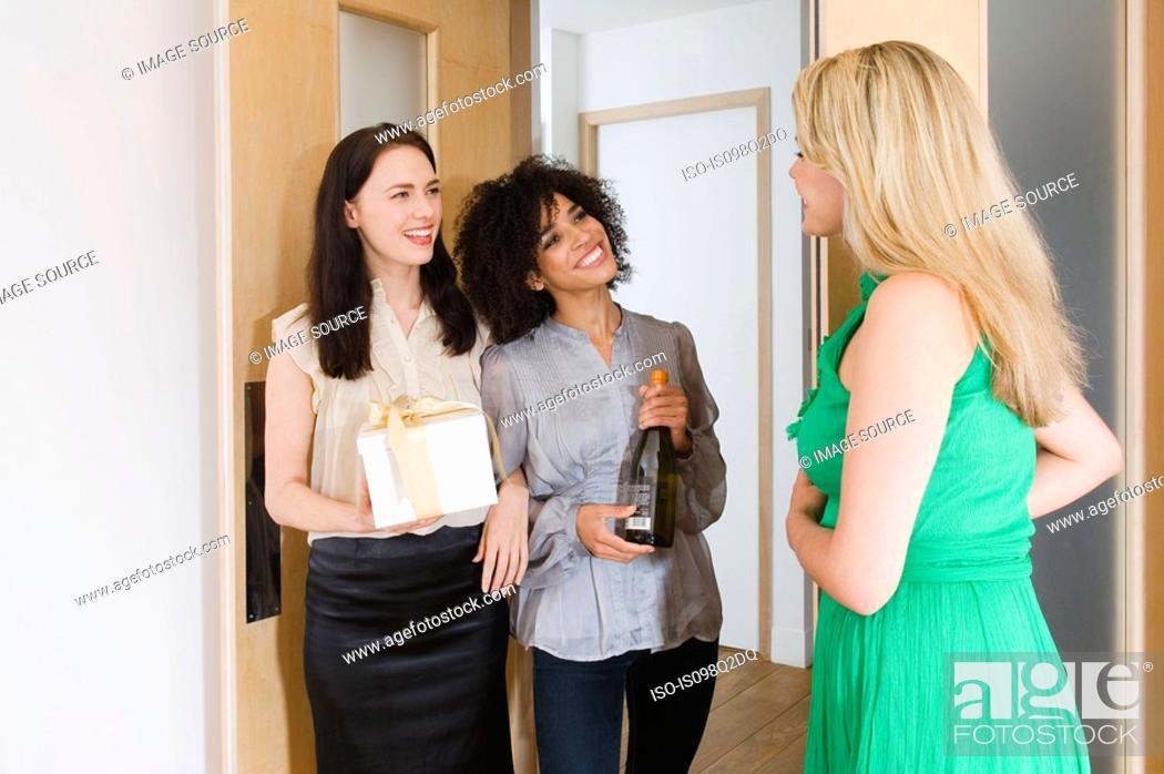 Stock Photo: A woman greeting friends at the door.