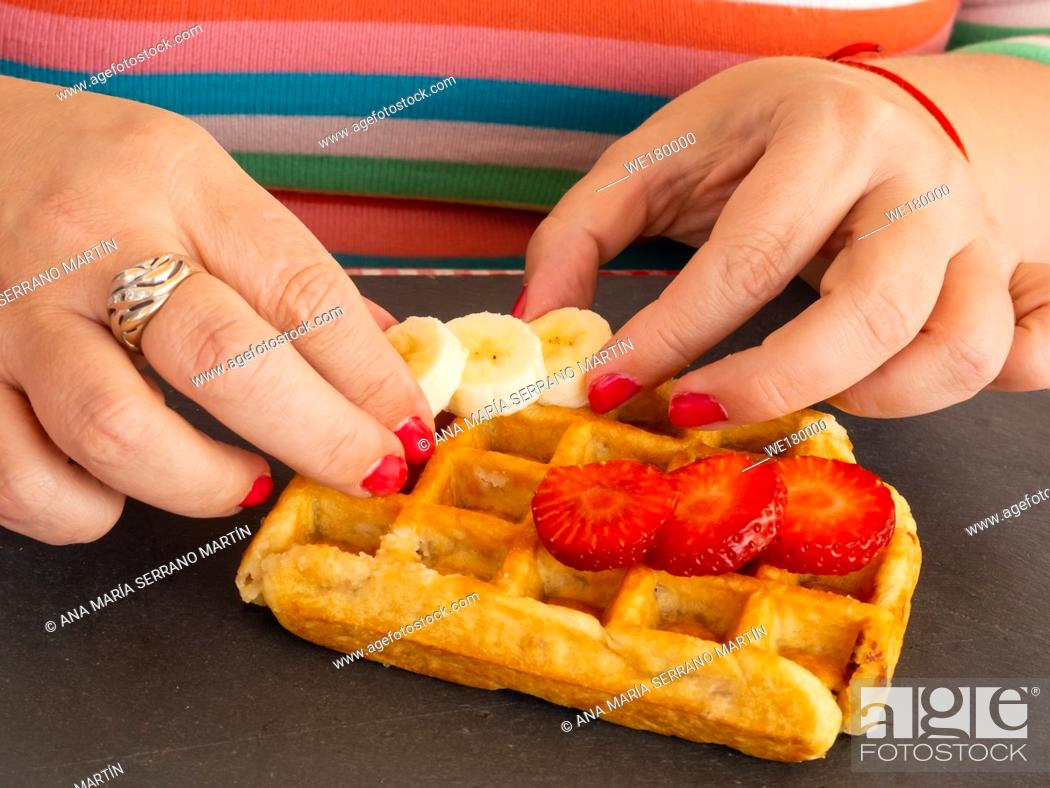 Stock Photo: A woman with red fingernails placing strawberry and banana pieces on a Belgian waffle.