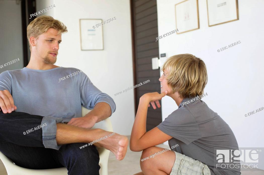 Stock Photo: Young man talking to a teenage boy.