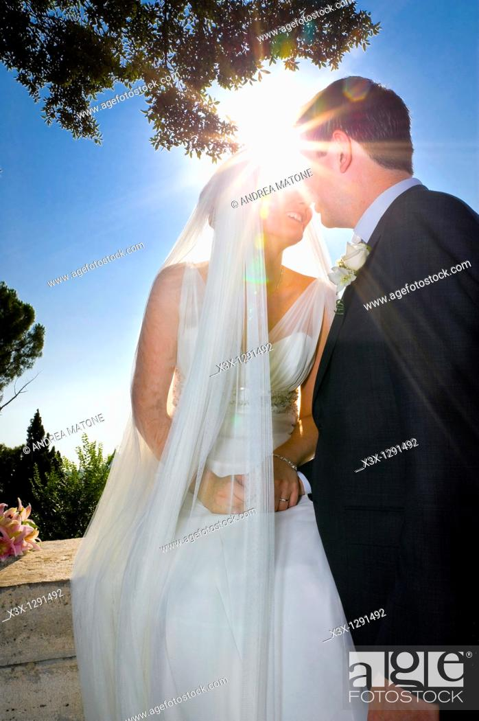 Stock Photo: Newlyweds kissing against the sun.