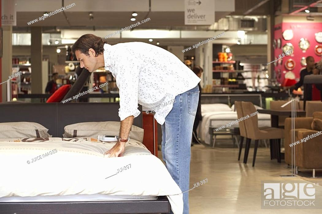 Stock Photo: Man testing mattress on new bed in furniture shop, bending down, side view.