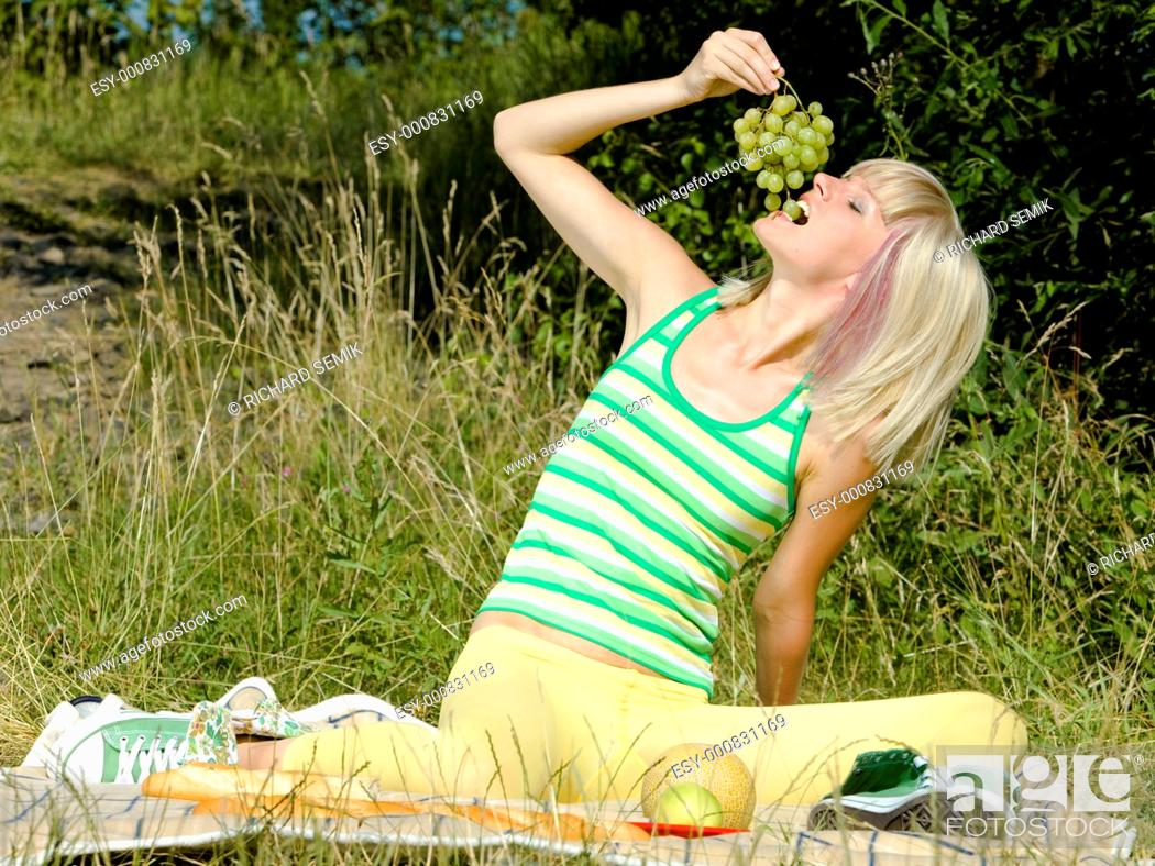Stock Photo: woman with grape at a picnic.