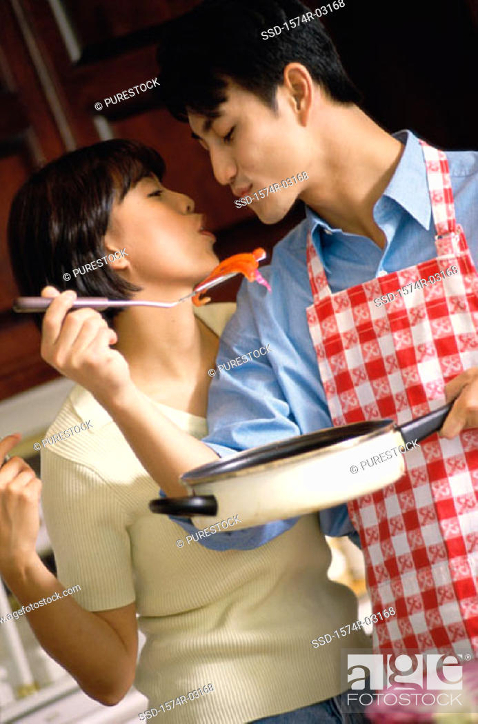 Stock Photo: Young man holding a pan and spatula kissing a young woman in the kitchen.
