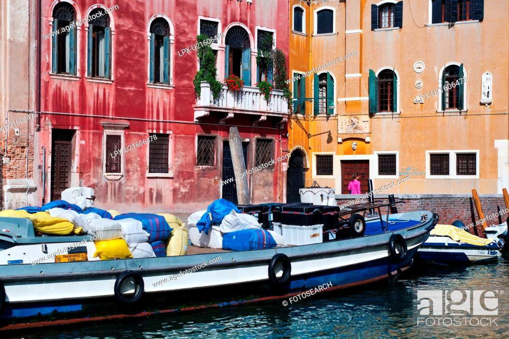 Stock Photo: Bright blue and white laden barge moored in front of red and yellow palazzi, with single woman in pink walking alongside canal, sunny autumn morning in Venice.