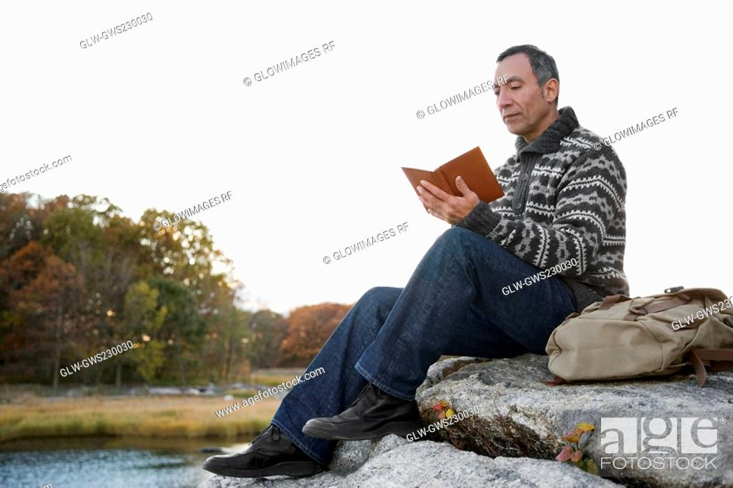 Stock Photo: Mature man sitting on a rock and reading a book.