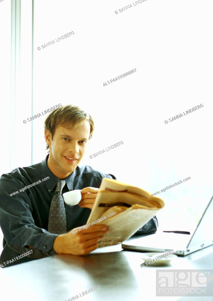 Stock Photo: Businessman sitting at desk, drinking and reading.