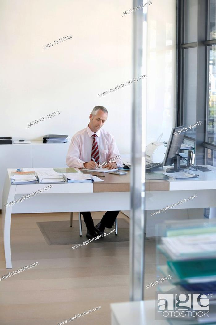 Stock Photo: Businessman sitting at desk in office working.