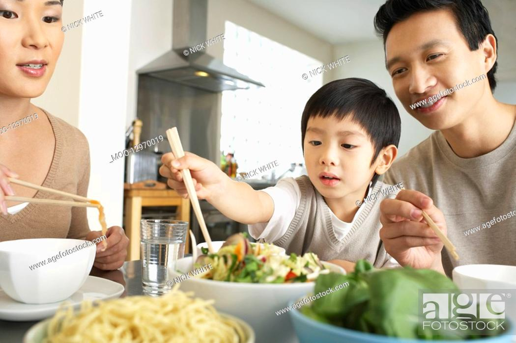 Stock Photo: Young parents sitting at table watching son trying to use chopsticks.