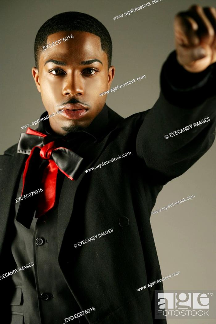 Stock Photo: Young African American man with fist up, studio shot.