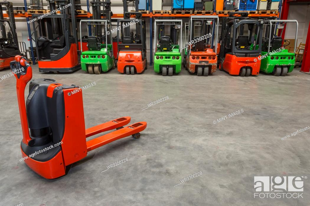 Stock Photo: Mechanical dolly and forklift machinery in warehouse.
