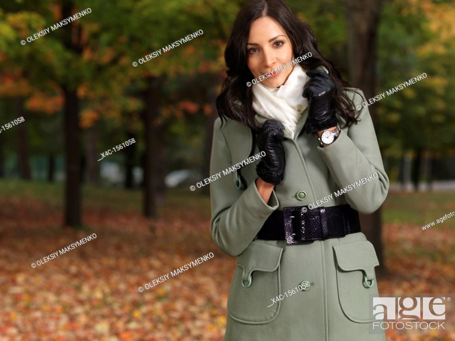 Stock Photo: Beautiful smiling woman wearing a green coat walking through a park in fall.