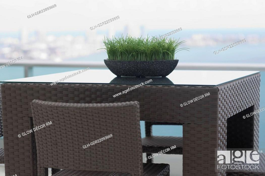 Imagen: Grass pot on table in the balcony of a house.